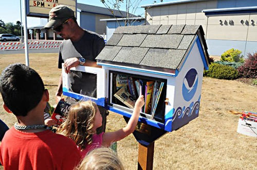 Youngsters line up to get a book from the Little Free Library in front of Sam Case Primary School Monday. A project of the Ford Family Leadership Program Central Lincoln County Cohort 3, 11 of the free Little Libraries are planned throughout the county. (Photo by Larry Coonrod)