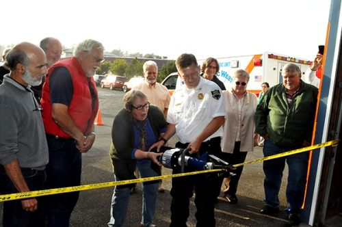Newport Mayor Sandy Roumagoux, center, assisted by acting fire chief Rob Murphy uses the Jaws of Life to cut the ribbon marking the official dedication of the Agate Beach Fire Station on NE 73rd Street. (Photo by Larry Coonrod)