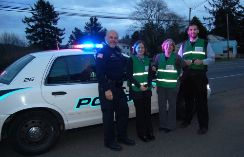 Lincoln City Police Department School Resource Officer Oscar Escalante poses with Oceanlake Elementary Principal Rilke Klingsporn, Taft High 7-12 Principal Majalise Tolan, and Taft Elementary Principal Nick Lupo, showing off the new two-way radios and green Incident Commander vests.