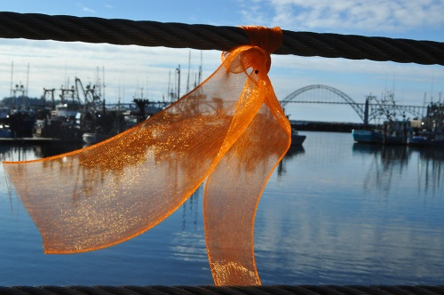 The Newport Fishermen's Wives along with friends and families of fishermen tied more than 100 orange ribbons along the Port of Newport boardwalk Friday symbolizing support for keeping a U.S. Coast Guard search and rescue helicopter stationed locally. (Photos by Larry Coonrod)