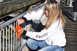 """Kelley Retherford ties a ribbon along the dock walkway. Retherford and her husband Mike own two fishing vessels crewed by all four of their children. """"A lot of my security came from knowing we did have that helicopter there,"""" she said. (photo by Larry Coonrod)"""