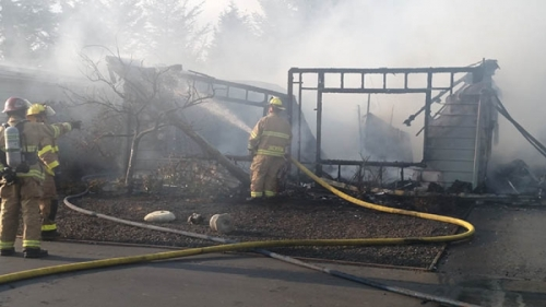 Firefighters from Newport, Depoe Bay and Toledo work to control a fire that destroyed one home in north Newport and damaged another Friday evening. Occupants of both residents and their pets escaped without injury. (Photo by Larry Coonrod)