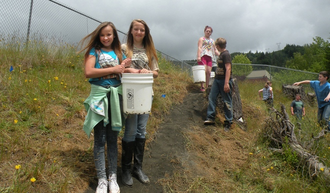 – From left, Talani Butler, Taunise Duarte, Savanna Kuchar and Scott Landis carry gravel in buckets to place on the trail. (courtesy photo)