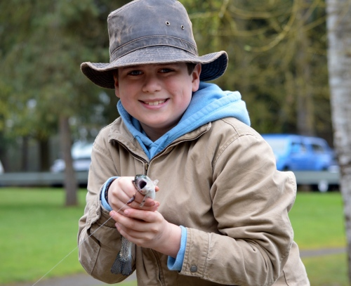 Zane Nilssen with his first fish, a rainbow trout that he caught at the Oregon Department of Fish and Wildlife's free youth fishing event at Canby Pond.